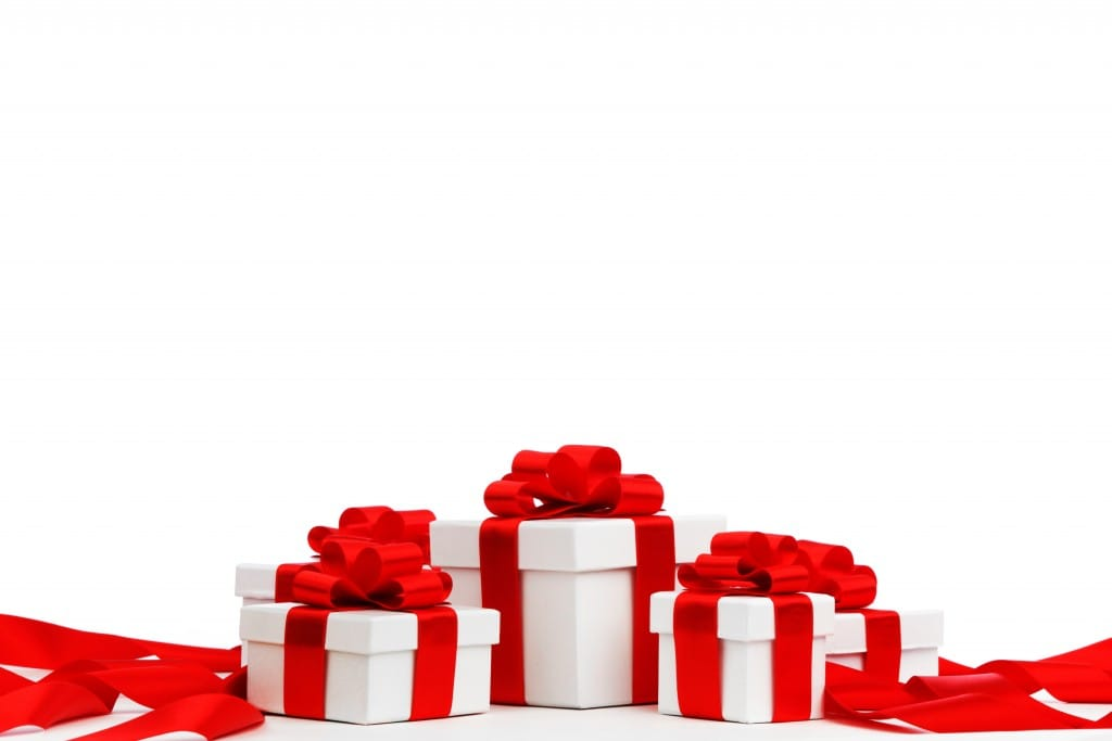 Holiday presents wrapped in white paper with red ribbons