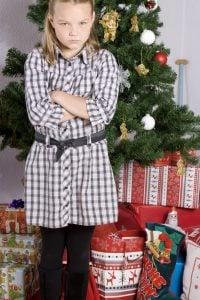 mdchen beleidigt vor dem weihnachtsbaum