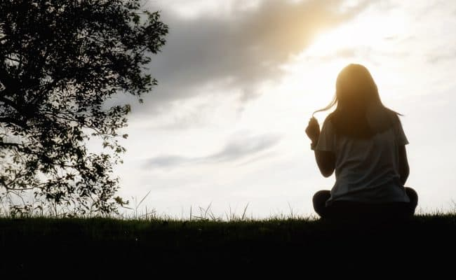 Sad and depressed woman sitting alone at the field during beautiful sunset with park background. Selective focus.